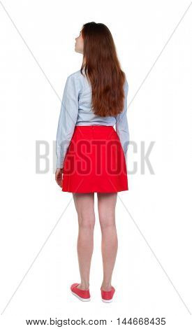 back view of standing young beautiful woman. Long-haired brunette in red skirt looks sideways.