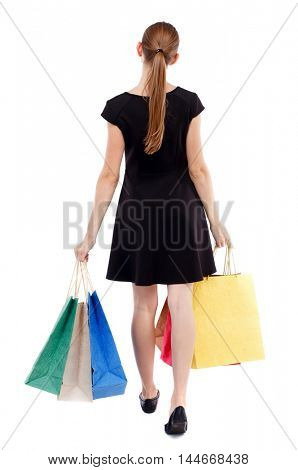 back view of going woman with shopping bags . beautiful girl in motion. Isolated over white background. Blonde in a short black bears purchases.