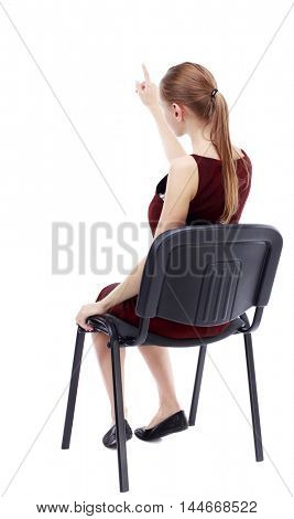 back view of young beautiful woman sitting on chair and pointing. girl in a burgundy dress sitting on a chair finger pointing.