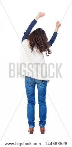 back view of dancing young beautiful woman. Long-haired girl with curly hair sways in time with the music.
