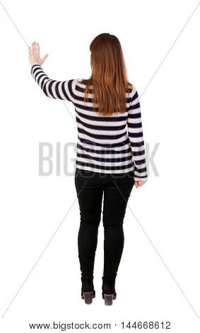 back view of young woman presses down on something. . Girl in a striped sweater hand presses the button.