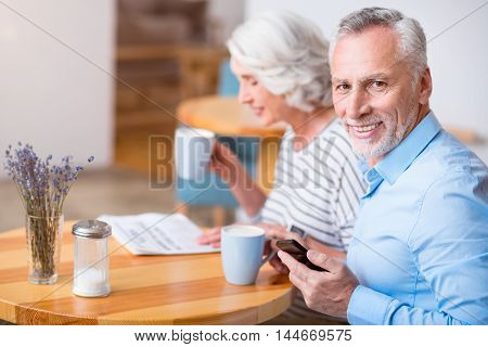 Involved in positive emotions. Cheerful senior man holding cell phone while drinking coffee and resting with his wife in the cafe