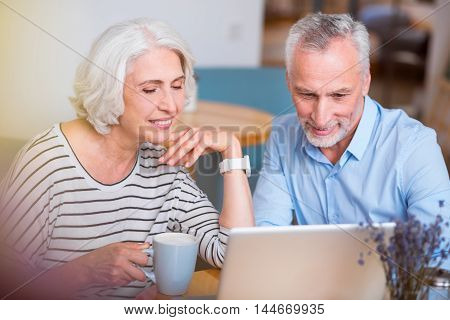 Enjoy every moment. Positive senior smiling couple sitting at the table and using laptop while resting in the cafe