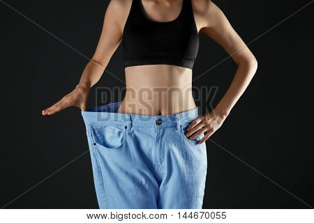 Girl in huge pants on black background