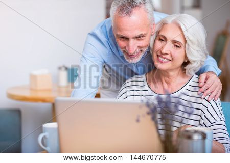 Spend spare time together. Delighted senior loving couple smiling and using laptop while resting in the cafe