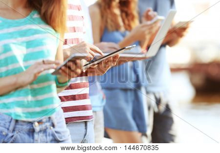 Young people with gadgets hanging out
