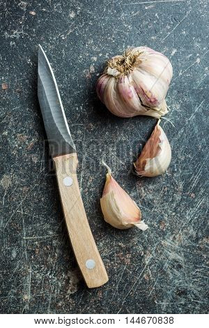 The fresh garlic with knife on kitchen table.