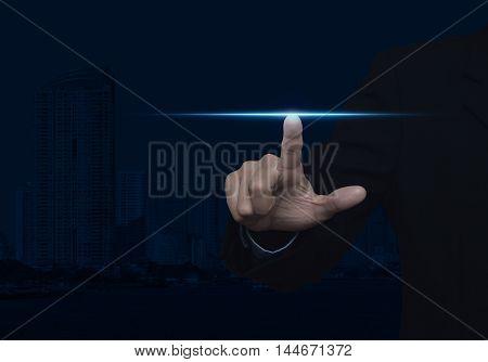 Businessman pressing blue power light over city background blue tone