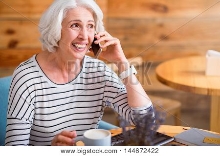 Full of gladness. Overjoyed smiling senior woman sitting at the table and talking on cell phone while resting