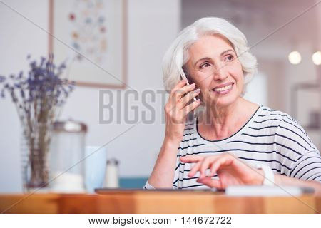 Best way to communicate. Cheerful senior woman smiling and sitting at the table while talking on cell phone