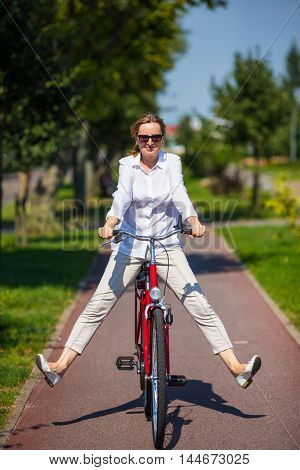 Urban biking - woman riding bike in city park