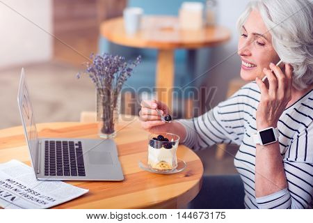 Sweet teeth. Cheerful smiling senior woman eating a dessert and talking on cell phone while resting in the cafe