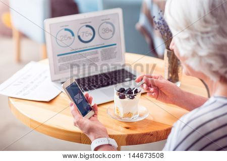 New message. Pleasant delighted senior woman sitting at the table and eating a dessert while sing cell phone