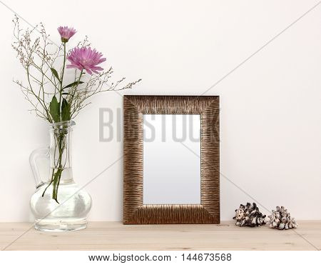Small bronze frame mockup with flowers and sea shells