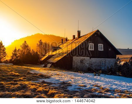 Mountain hut in first beams of rising sun. Freezy mountain morning in winter time.