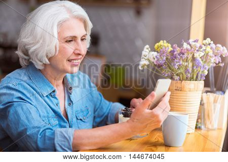 Nice start of the day. Pleasant delighted senior woman using cell phone and having a breakfast while sitting in the cafe