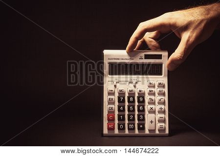 Male Hand Holding A Electronic Calculator