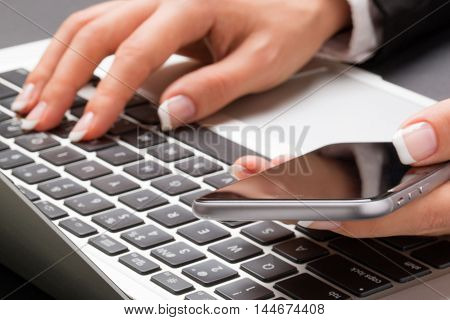 Young office woman in the black suite and with manicure is typing with one hand on the laptop keyboard and holding the smartphone with another one.