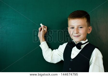 Little smiling student writing on the blackboard with chalk