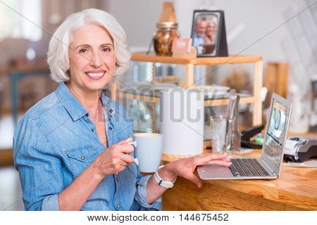 Full of positivity. Cheerful content senior woman drinking coffee and using laptop while resting in the cafe