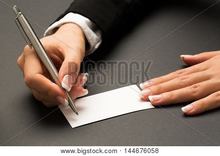 Office woman in black suite with manicure is writing with the metal pen on a blank white contact card