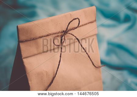 Package for lunch on a blue background. Gift kraft bag tied with twine (vintage)