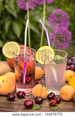Fresh lemonade and ripe fruits on wooden table