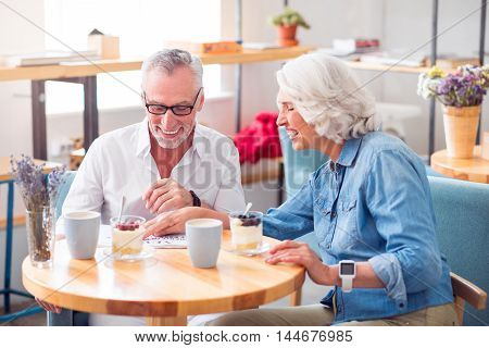 Overwhelmed with emotions. Overjoyed content senior couple smiling and reading newspaper while resting at the table in the cafe