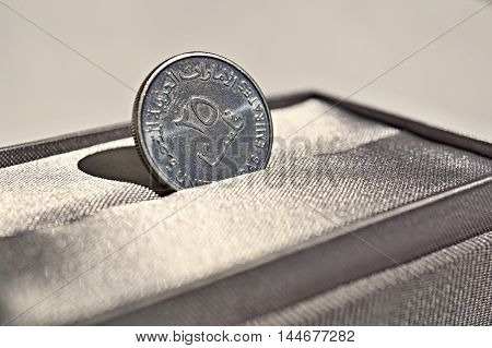 Macro detail of a silver coin of Dirham (United Arab Emirates Dirham, AED) placed in the gray luxurious jewelry gift box as a symbol of luxury and highly appreciated currency of the Emirates (UAE)
