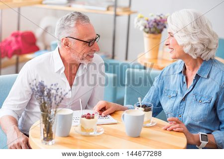 Share ideas. Positive content senior couple sitting in the cafe and talking while having a breakfast