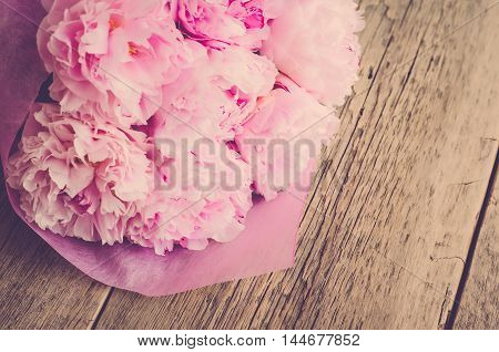 Bouquet of peonies in a pink wrapper on a wooden background (vintage)