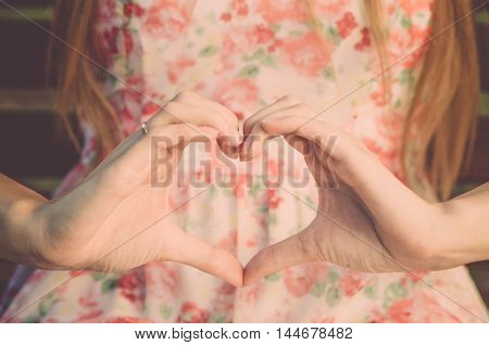 Girl in dress sitting and making a heart shape out of her hands (vintage)