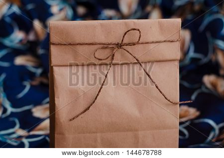 Kraft bag for gifts. Package products. Package for lunch tied with rope brown