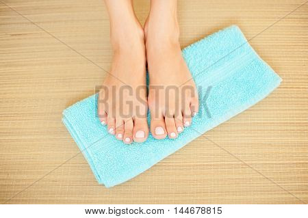 Close-up shot of beautiful woman feet with French pedicure on blue towel