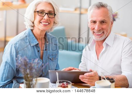 Enjoy this time. Joyful delighted smiling couple using tablet and sitting at the table while having breakfast