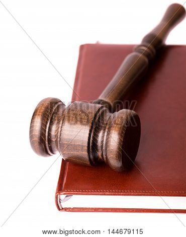 Wooden gavel on leather binding book from right side on white