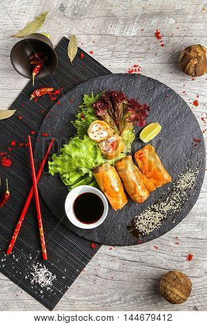 Spring rolls with vegetables and chopsticks on a stone plate, view from the top