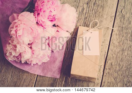 Gift for women: flowers peonies and kraft bag with white tag on wooden background (vintage)