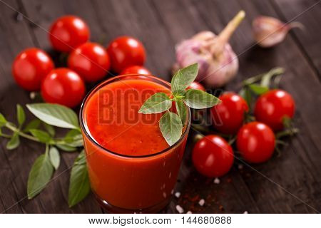 Tomato juice glass with basil and tomatoes on old wooden table
