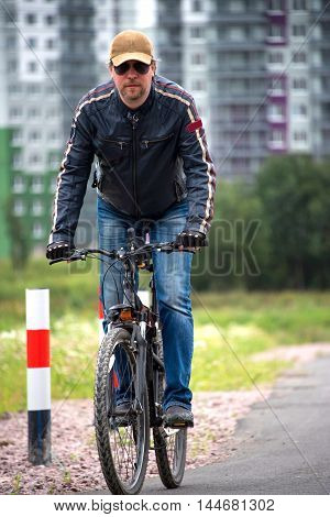 Man in a leather jacket rides a Bicycle