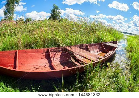 Old wooden fishing boat at the lake in summer day