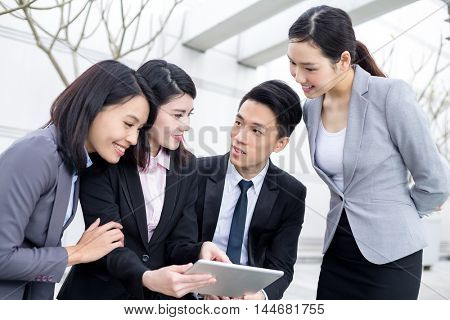 Group of business people discuss on tablet
