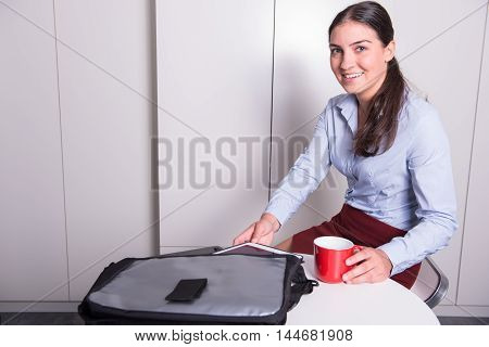 professional female is taking out tablet during coffee break