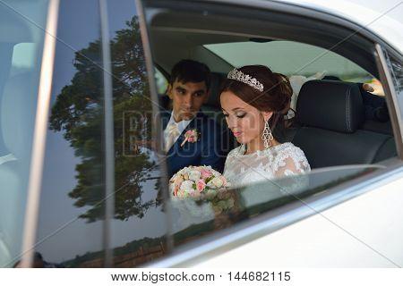 Happy romantic newlyweds, bride and groom sitting in wedding car.