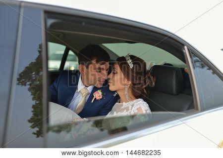 Happy romantic newlyweds, bride and groom kissing in wedding car.