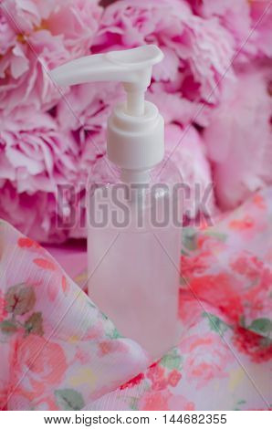 The tube with liquid soap on a pink colored background