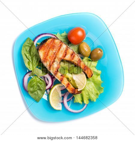 Grilled salmon steak with sliced onion and tomatoes on blue plate isolated on white top view