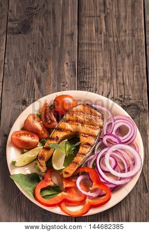 Grilled salmon steak with sliced onion and tomatoes on old wooden table