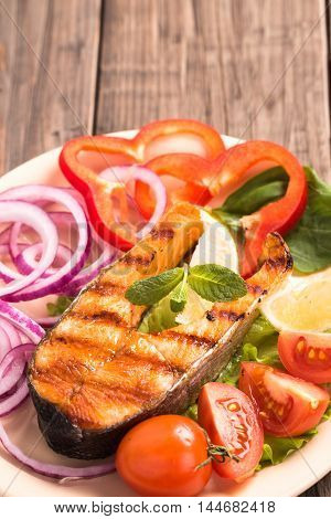 Grilled salmon steak with sliced onion and tomatoes on old wooden table vertical
