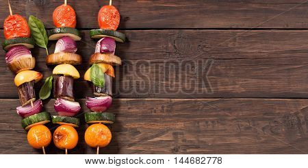 Grilled veggie skewers at left side old rustic wooden background with copy space